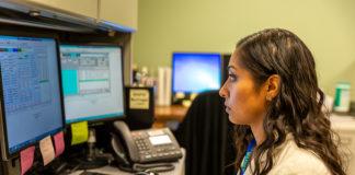 Noelia Salgado works at desk on computer.