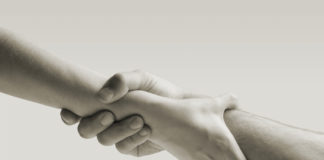 Image of outstretched hands clasping. Reaching out for help.