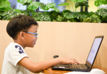 Photo of small child learning how to code.