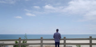 Wide shot of The Last Mile graduate looking out at the ocean.