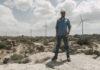 Wind Turbine Technician James Van Dyken stands in front of wind farm.
