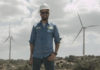 Wind Turbine Technician James Van Dyken stands in front of wind farm.
