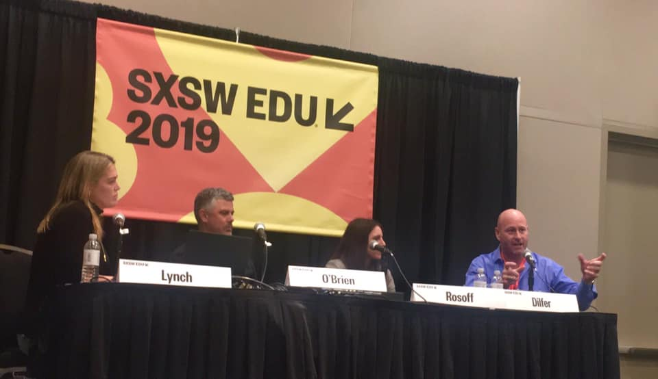 Panelists sit at table on stage for panel discussion at SXSW EDU.