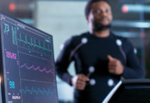 Male Athlete Runs on a Treadmill with Electrodes Attached to His Body while Sport Scientist Holds Tablet and Supervises EKG Status in the Background.