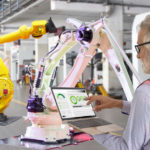 Engineers use laptop computers for machine maintenance, automation tools, robot arm at the factory.