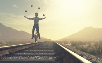 Juggler is balancing on railroad with a bike and balls.