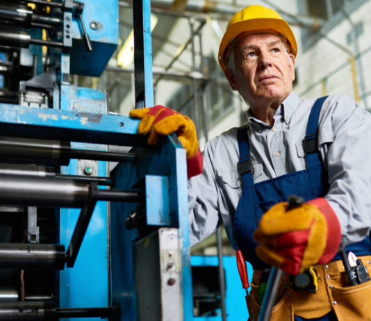 Low angle portrait of senior factory worker standing by machine in modern industrial workshop.