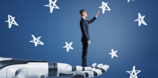 A businessman stands on a giant robotic arm and reaches to chalk-drawn stars.