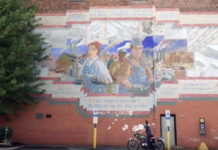 YorkEx CEO John McElligott on his motorcycle below the York Plan mural in York, Pennsylvania.