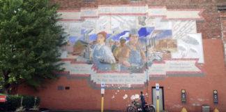 YorkEx CEO John McElligott on his motorcycle below the York Plan mural in York, Pennsylvania.