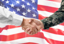 Soldier and civilian shaking hands on USA flag background