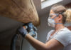 Woman sanding wood beam in home