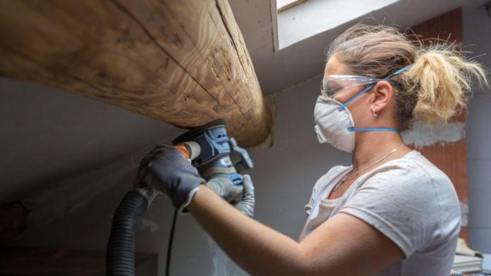 Woman sanding wood beam in home
