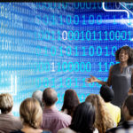 Woman stands in front of students with binary code graphic in background
