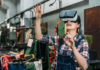 Young woman wears Virtual Reality goggles in factory